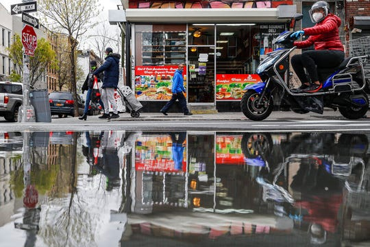 """In this April 27, 2020, file photo, pedestrians and motorists wear personal protective equipment as they pass a small grocery that is one of the few businesses open on the street in New York. As some governors across the United States begin to ease restrictions imposed to stop the spread of the coronavirus, hopes are soaring that life as we knew it might be returning. But the plans emerging in many states indicate that """"normal"""" is still a long way off."""