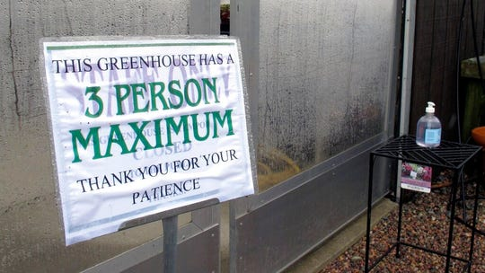 In this Monday, April 27, 2020, photo, with a bottle of hand sanitizer in the background, a sign limits the number of shoppers in the greenhouse of Evergreen Gardens of Vermont in Waterbury Center, Vt.