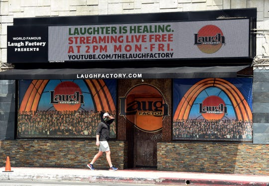 """In this April 20, 2020 photo, a pedestrian walks underneath a marquee advertising a """"Laughter is Healing"""" stand-up comedy livestream event at the Laugh Factory in Los Angeles. With comedy clubs closed and concert tours put on hold, comics like Craig Robinson, Tiffany Haddish, Will C  and others are keeping the jokes flowing on webcasts and Zoom calls even without the promise of a payday, because they say the laughs are needed now more than ever."""