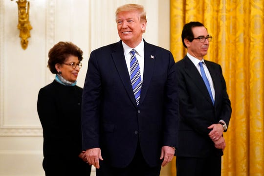 President Donald Trump smiles during an event about the Paycheck Protection Program used to support small businesses during the coronavirus outbreak, in the East Room of the White House, April 28, 2020, in Washington. At left is Jovita Carranza, administrator of the Small Business Administration and Treasury Secretary Steven Mnuchin, watching.