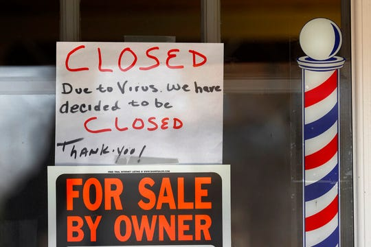 "In this April 2, 2020 file photo, ""For Sale By Owner"" and ""Closed Due to Virus"" signs are displayed in the window of a store in Grosse Pointe Woods, Mich. The second round of loan applications for the government's small business relief program has been slowed by computer issues at the Small Business Administration. Lenders complained Monday, April 27, that they couldn't get their applications into the SBA system known as ETran that processes and approves loans."