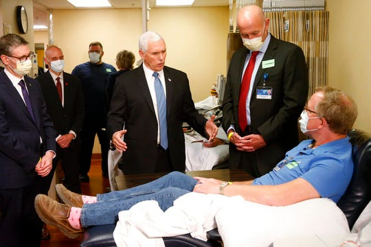 Vice President Mike Pence, center, visits a patient who survived the coronavirus and was going to give blood during a tour of the Mayo Clinic Tuesday, April 28, 2020, in Rochester, Minn., as he toured the facilities supporting COVID-19 research and treatment. Pence chose not to wear a face mask while touring the Mayo Clinic in Minnesota. It's an apparent violation of the world-renowned medical center's policy requiring them.