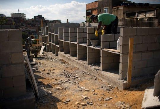 Workers build new niches for victims and suspects of COVID-19 at the Nossa Senhora das Gracas cemetery in Duque de Caxias, Rio de Janeiro, Brazil, Monday, April 27, 2020.