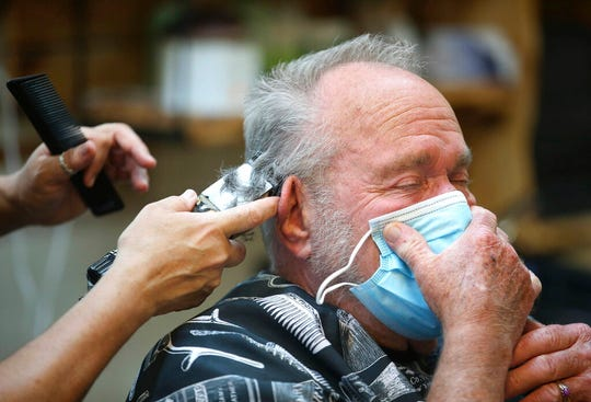 In this April 24, 2020, file photo, Lonnie Sullivan covers his face with a mask while getting a haircut at The Barber Shop in Broken Arrow, Okla.