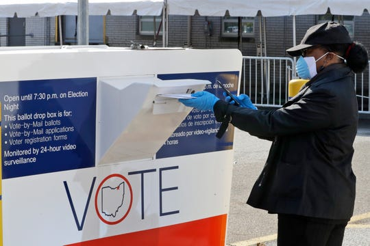 Marcia McCoy drops her ballot into a box outside the Cuyahoga County Board of Elections, Tuesday in Cleveland, Ohio.