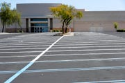 An idle business and empty parking lots are shown Saturday, April 4, 2020, in Chandler, Ariz.
