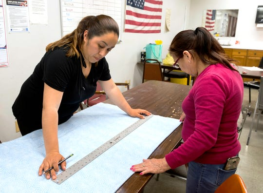 Don's Claytons employees Carolina Robliro, left, and Briselda Gonzalez, right, draw out patterns for face masks Monday afternoon, April 27, 2020. The local dry-cleaning chain is offering free masks for the community amid the COVID-19 pandemic.
