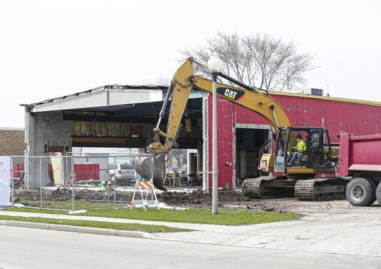 A construction worker uses an excavator Tuesday, April 28, 2020 at the site of the old Parrot Palms building on North Hickory Street in Fond du Lac, Wis. The former bar closed its doors on April 13, 2014.