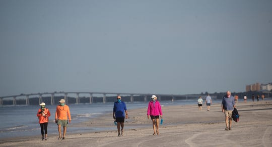 People  walk on Fort Myers Beach Tuesday, April 28, 2020. The Fort Myers Beach Town Council allowed the beaches to open to residents only. Face masks were mandatory as well.