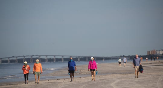 People  walk on Fort Myers Beach Tuesday, April 28, 2020. The Fort Myers Beach Town Council allowed the beaches to open to residents only. Face masks were mandatory as well. It appeared as residents were abiding by social distancing guidelines. The County Commission voted Tuesday to reopen all public beaches starting Wednesday morning.