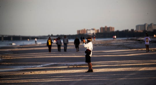 Dennis Driscoll takes photos on Fort Myers Beach on Tuesday, April 28, 2020. The Fort Myers Beach Town Council allowed the beaches to open to residents only. Face masks were mandatory as well. It appeared as residents were abiding by social distancing guidelines. The County Commission voted Tuesday to reopen all public beaches starting Wednesday morning. Driscoll has an R.V. and gets his mail at an R.V. Park in San Carlos Island