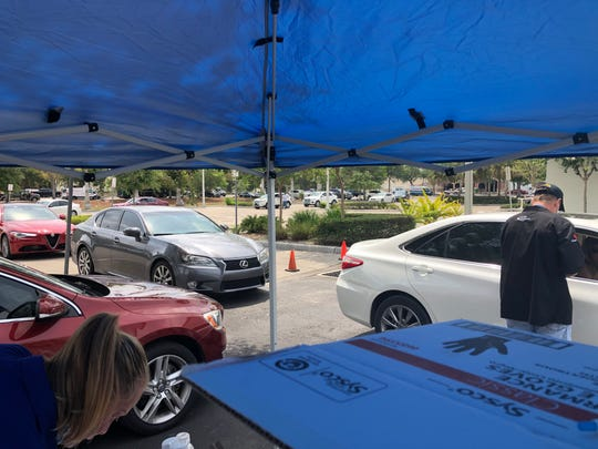 Sysco employees swipe credit cards and distribute food at last Friday's drive-through grocery store event at Southwest Florida Event Center.