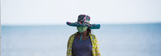 Fort Myers Beach resident Lien Ton takes a stroll on Fort Myers Beach while wearing a face mask on Tuesday, April 28, 2020.
