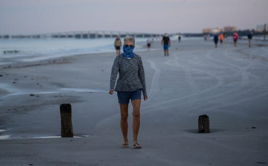 Fort Myers Beach resident Marsha Disharoon takes a stroll on Fort Myers Beach Tuesday, April 28, 2020. The Fort Myers Beach Town Council allowed the beaches to open to residents only. Face masks were mandatory as well. It appeared as residents were abiding by social distancing guidelines.  From a town of Fort Myers Beach press release.  The Lee County Commissioners voted today to re-open County-controlled public beaches effective Wednesday, April 29, 2020. This impacts the beach from Crescent Beach Park including Lynn Hall Memorial Park (pier) northward and Bowditch Point Park. However, beach and accesses controlled by the Town of Fort Myers Beach (from Crescent Beach Park south to Big Carlos Pass Bridge) remain open from 7 a.m. to 10 a.m. for residents' exercise only. Beach access parking controlled by the Town remains closed. Enforcement of parking and beach access violations will be in effect. The Town's parks, recreation and cultural facilities, as well as Town Hall, remain closed until at least Friday, May 1, 2020, when Town Council is scheduled to meet for further discussion on beach openings and related topics. When the Lee County beaches open tomorrow, the general public is advised to stay in and north of Crescent Beach Park.