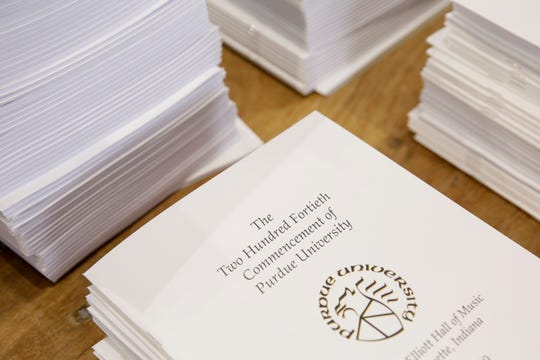 Stacks of commencement programs sit on a table inside the Purdue Armory as volunteers assemble packages with graduation materials to be shipped to graduating Purdue students, Tuesday, April 28, 2020 in West Lafayette.