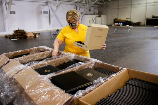 Volunteers work to assemble packages with graduation materials to be shipped to graduating Purdue students, Tuesday, April 28, 2020 in West Lafayette.