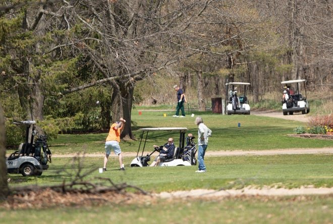 Golfers on the fifth and 13th holes of Hawk Meadows Golf Course in Howell use golf carts Tuesday, April 28, 2020.