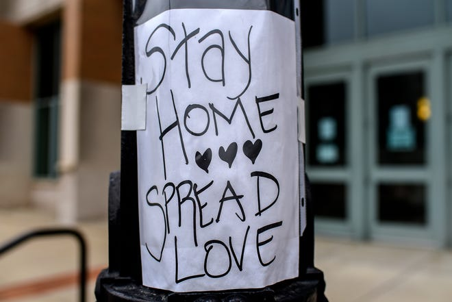 """Signs reading """"Stay home, spread love"""" were displayed on light posts on Michigan Avenue between Pennsylvania Avenue and Grand avenues on April 27, 2020, in Lansing."""