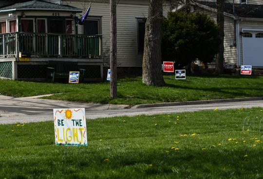 Signage seen in yards near Pleasant and Spring Streets in downtown Grand Ledge Tuesday, April 28, 2020.