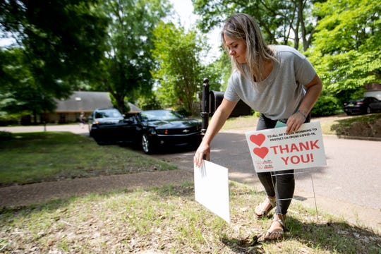 Averi Davis places a thank-you sign in a yard Tuesday, April 28, 2020, in Germantown.