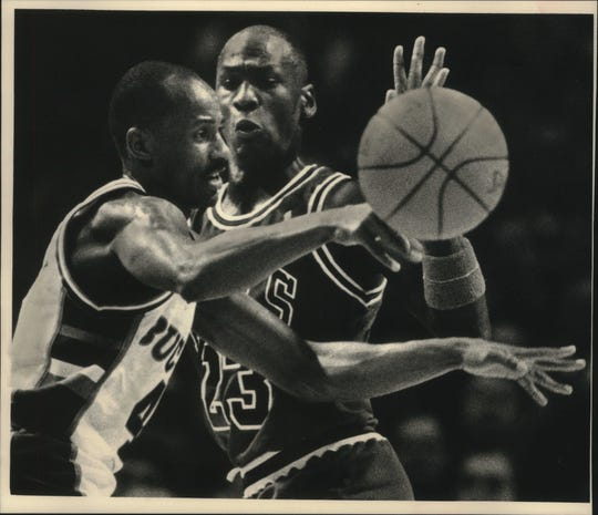 Bucks guard Sidney Moncrief dishes off as Chicago's Michael Jordan nears in 1988.