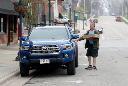 Van Christenson of Hartford takes a couple of pizzas to his car that he got for carryout at The Mineshaft Restaurant on Main Street in Hartford on Tuesday.