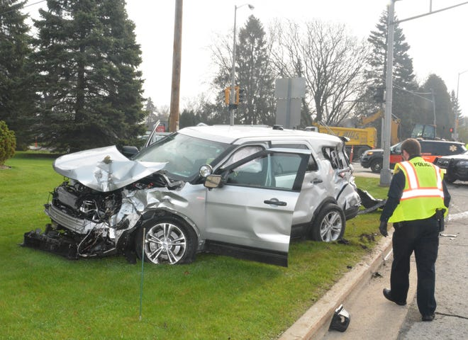 A law enforcement officer surveys the damage done to a New Berlin Police Department squad car in a four-vehicle crash Tuesday morning, April 28, near 124th Street and Cleveland Avenue in New Berlin. The driver of the squad and another person were taken to the hospital with what police described as non-life-threatening injuries.