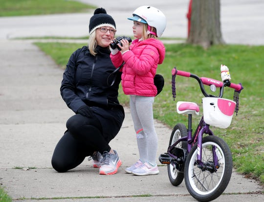 Lybra Loest and her daughter, Finley, 5, get ready to take a look at the owls in a group of trees on East Newton Avenue in Shorewood on Tuesday.