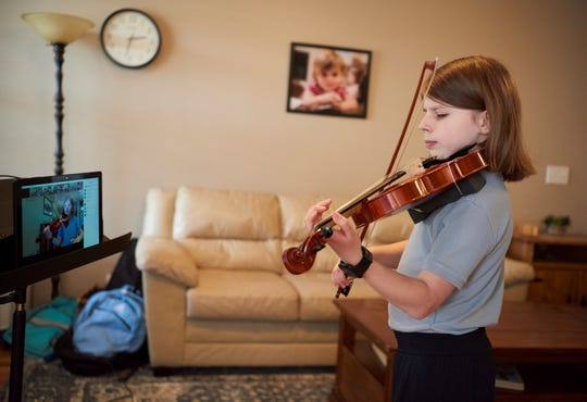 Anna Drummonds, a student at Vanderbilt's Blair School of Music, plays the violin in front of a tablet at her home during an online performance for an older Nashville resident.