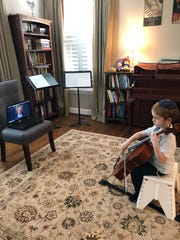 Ezra Ebin, a student at Vanderbilt's Blair School of Music, plays his instrument in front of a laptop at his home during an online performance for an older resident.