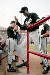 Former NBA great Michael Jordan, center, gets a high-fives from a teammate after making a play in the outfield for the Birmingham Barons against the Nashville Xpress in the first game of a double header at Greer Stadium Aug. 2, 1994.