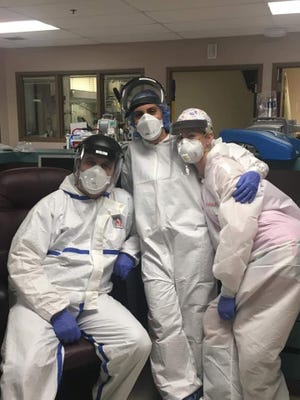 Dr. Matthew King (left) in a photograph with two colleagues as he works the front lines of the coronavirus pandemic. King is a critical care doctor at Sumner Regional Medical Center working in the COVID unit.