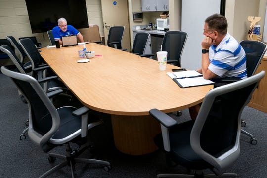 Principal Jon Bremseth, left, talks to Assistant Principal Sean McAndrews from the opposite end of a conference table during a morning staff meeting at Barron Collier High School in Naples, Fla., on April 23.