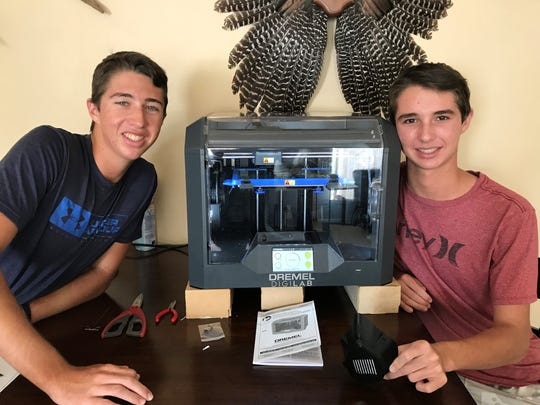 Marco Island Academy students Tyler and Colby Chute sit next to a 3D printer.