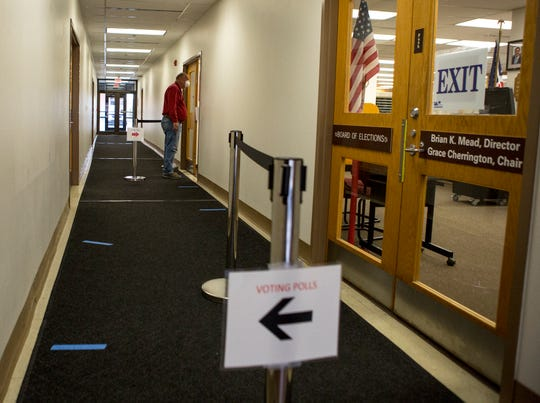 A man waits, as signs direct him to go to the counter to receive his ballot for in-person voting Tuesday at the Licking County Board of Elections. Most Ohioans voted by mail-in ballot but those whose ballots did not arrive in time were permitted to vote in person.