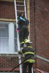 Passaic firefighter Ricky Figueroa and Deputy Fire Chief Christopher DiBella rescue a child from a third-floor window on Dayton Street in Passaic on Monday afternoon, April 27, 2020.