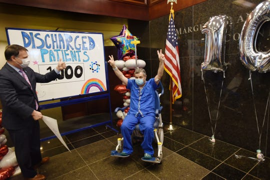 Karan Omidvari of Manhattan, who is discharged with special clap-out as the 1000th COVID-19 Positive Patient at Hackensack University Medical Center, is celebrated by staff together with Mark Sparta (L), President of Hackensack University Medical Center, at the lobby on April 28, 2020.