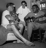 """Tackle Roosevelt """"Rosey"""" Grier, right, and linebacker Harland Svare, left, of the New York Giants football team tune up their guitars following training camp at Bear Mountain, New York, on August 27, 1959. Rookie quarterback Lee Grosscup, watches."""
