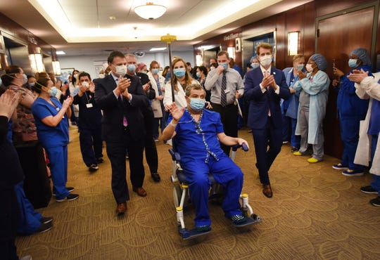 Karan Omidvari of Manhattan, who is discharged with special clap-out by the hospital staff as the 1000th COVID-19 Positive Patient at Hackensack University Medical Center, is escorted to the lobby on April 28, 2020.