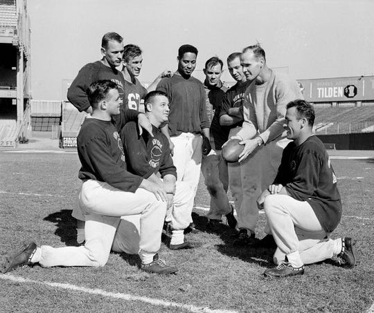 Defensive backfield coach Tom Landry holds ball as New York Giant defense men huddle Nov. 6, 1958 during workout at Yankee Stadium in New York. They will be called on Nov. 9 to stop the passing and running attack of the undefeated Baltimore Colts. From left to right are; kneeling, linebacker Harland Svare, middle guard Sam Huff and back Cliff Livingston. Standing, backs Carl Karilivacz, Jim Patton, Em Tonnell, Linebacker Bill  Svoboda, back Lindon crow and Landry.