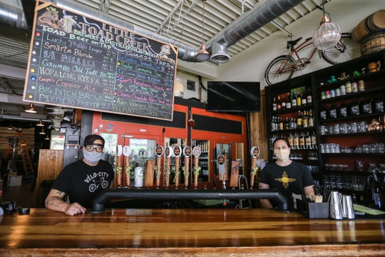 Michael Ponce and Carol Ayon wear masks behind the bar at Little Toad Creek Brewery and Distillery in Downtown Las Cruces on Tuesday, April 28, 2020. Because of the state liquor laws, customers must pick up growlers of beer or spirits by the bottle on Little Toad's patio, within its premises.