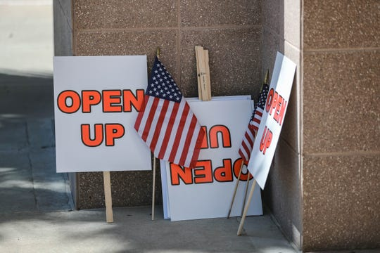 Protest signs lay at the entrance of the Doña Ana County Commission Chambers in Las Cruces on Tuesday, April 28, 2020.