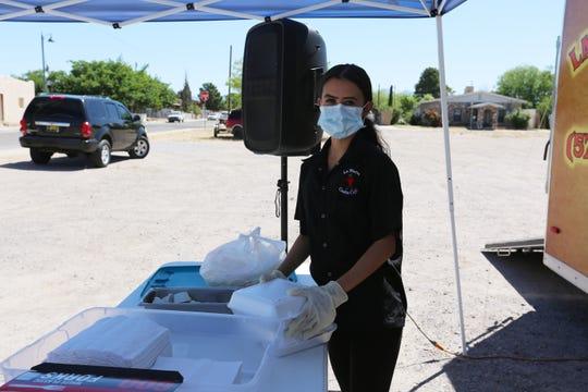 Leslie Paredes helps serve the community free enchilada plates at La Nueva Casita Café on Tuesday, April 28, 2020.
