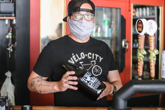 Michael Ponce is pictured behind the bar wearing a mask at Little Toad Creek Brewery and Distillery in Downtown Las Cruces on Tuesday, April 28, 2020.