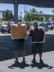 Cathedral City High School ASB Director George Howell, left, and Principal Guillermo Chavez help distribute food to students.