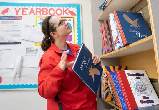 English teacher and yearbook director MaryJane Gardner rearranges archive yearbooks in her empty Pine Forest High School classroom during the coronavirus shutdown in Pensacola on Tuesday, April 28, 2020.  Gardner can't wait to return to her classroom when the schools reopen.