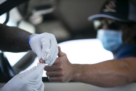 Phoenix firefighter Ryan Teefy receives a free antibody test for the new coronavirus, administered by Phoenix firefighter paramedics at the Phoenix Fire Department training facility in Phoenix on April 28, 2020.