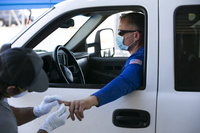 Phoenix firefighter Rick Rewerts (right) receives a free antibody test for the new coronavirus, administered by Phoenix firefighter paramedic Nate Byrd at the Phoenix Fire Department training facility in Phoenix on April 28, 2020. Antibody tests do not test for the presence of COVID-19 itself, but detect whether someone has the antibodies in their immune system to fight off the virus. Within 10 minutes after taking the test that first responder was notified by phone if they tested positive. The tests, available to all members of the Phoenix Fire Department, were organized by the United Phoenix Firefighters Association.