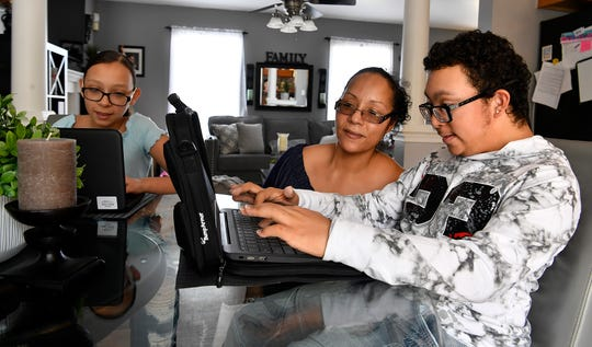 Elizabeth Silva, center, has been helping her children, including Izabelle, 14 at left, and AJ, 15, with their school work during the COVID-19 shutdown. Tuesday, April 28, 2020.John A. Pavoncello photo