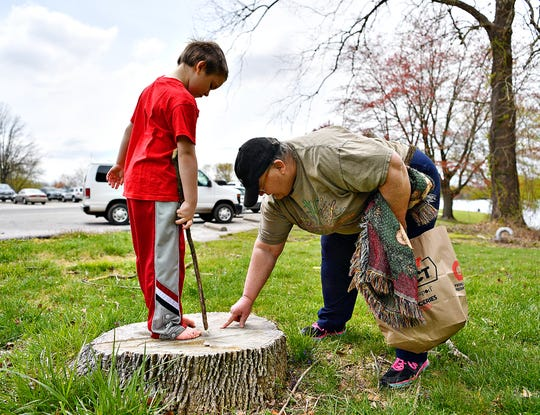 Wendy Looker, of Hanover, explains how the rings of a tree trunk show the age of a tree to her grandson Aydan Looker, 6, at Codorus State Park in Codorus Township, Saturday, April 25, 2020. Looker, a retired environmental educator, uses everyday moments to teach her grandson as the pair frequent the park outside of Aydan's remote learning during the pandemic. Dawn J. Sagert photo